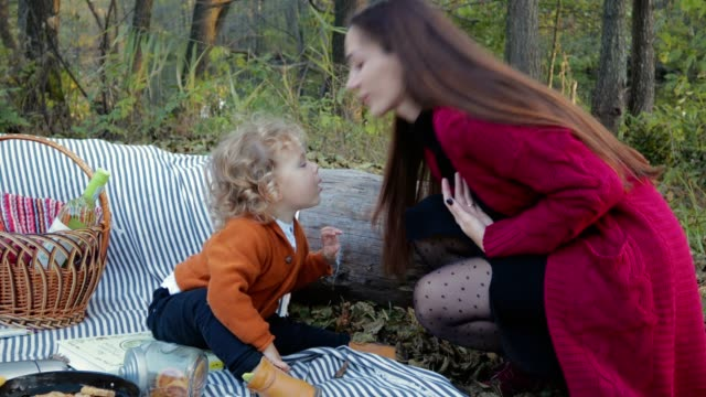Happy-mother-kissing-her-child-on-a-picnic-in-the-woods-and-gives-him-the-phone