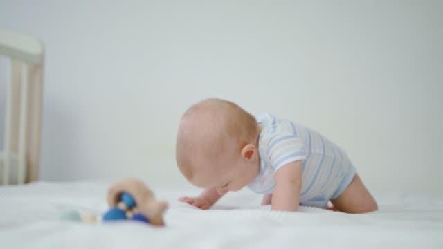 Niedliche-Baby-krabbeln-auf-ihrem-Bett-zu-Hause