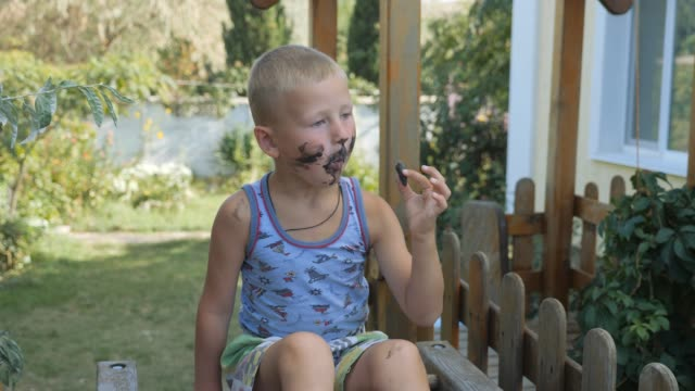 Child-eats-ice-cream-boy-smeared-his-face-with-food-Kid-eating-ice-cream-from-a-black-waffle-cone-
