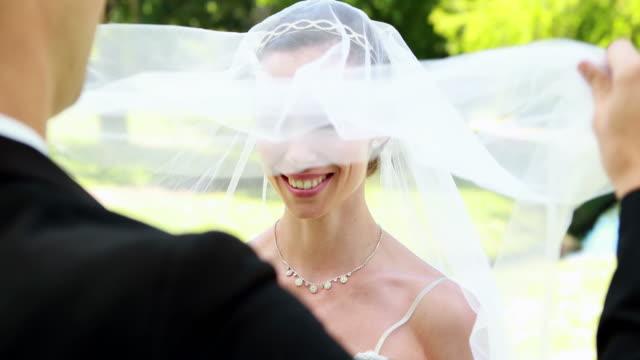 Bräutigam-lifting-Schleier-der-Braut-Gesicht-strahlenden