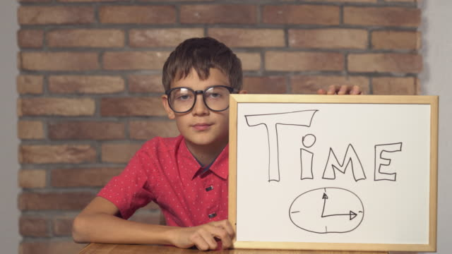child-sitting-at-the-desk-holding-flipchart-with-lettering-time-on-the-background-red-brick-wall