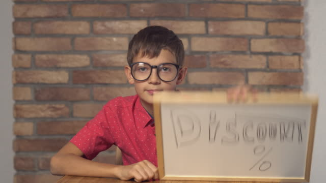 child-sitting-at-the-desk-holding-flipchart-with-lettering-discount-on-the-background-red-brick-wall