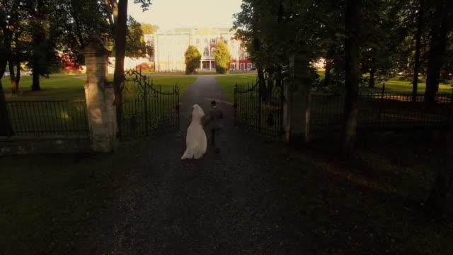 Toma-aérea-drone-de-un-novio-y-la-novia-hacia-la-mansión-en-un-parque-