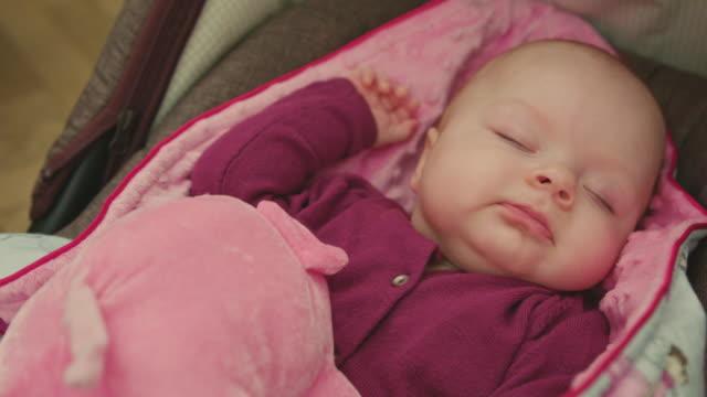 Schlafendes-Baby-mit-Spielzeug-dreht-ihren-Kopf