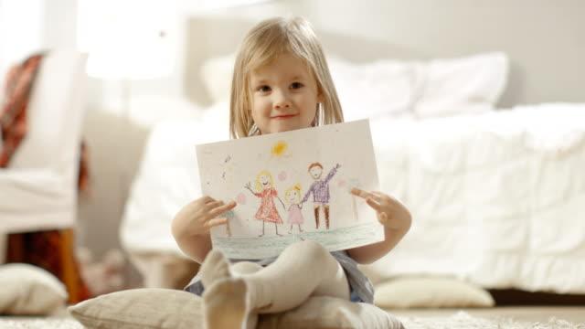Linda-chica-joven-sentado-sobre-almohadas-muestra-el-dibujo-de-su-familia-