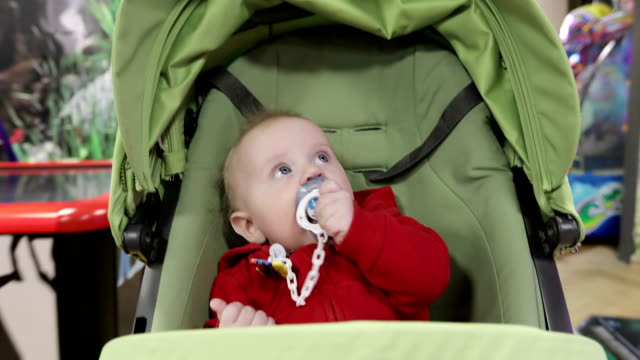 A-little-boy-going-in-the-stroller-and-playing-with-his-nipple-Cute-baby-is-on-a-walk-in-the-entertainment-center-