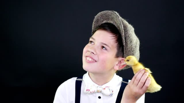 Portrait-a-pretty-boy-in-a-cap-and-suspenders-plays-with-a-small-yellow-duckling-Studio-video-with-thematic-decoration