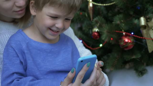 Niño-feliz-y-su-madre-en-el-teléfono-inteligente-cerca-de-árbol-de-Navidad