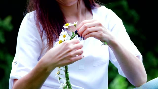 Summer-Portrait-In-the-middle-of-a-chamomile-lawn-in-a-forest-a-young-woman-a-brunette-wove-a-wreath-of-chamomiles