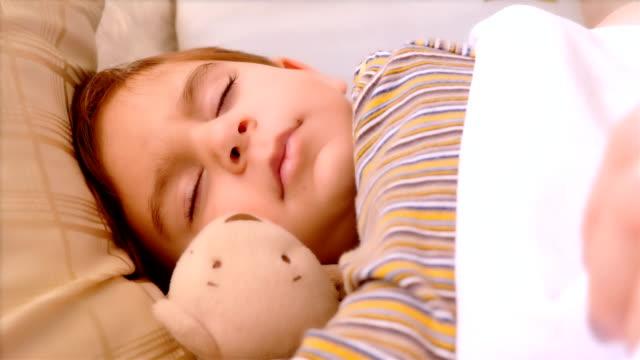 Retrato-de-niño-de-3-años-de-edad-dormir-con-el-oso-de-peluche-La-mano-de-la-madre-que-le-cubre-con-la-manta-