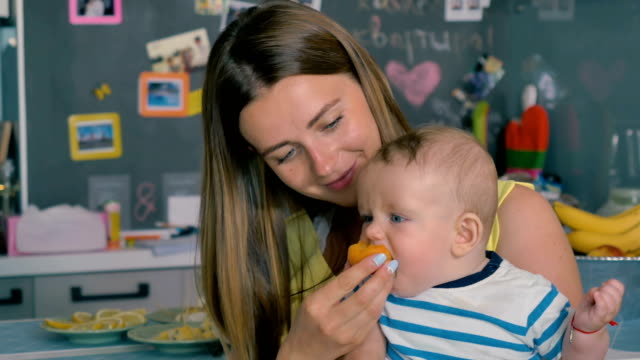 Young-mother-feeds-her-little-son-with-an-apricot