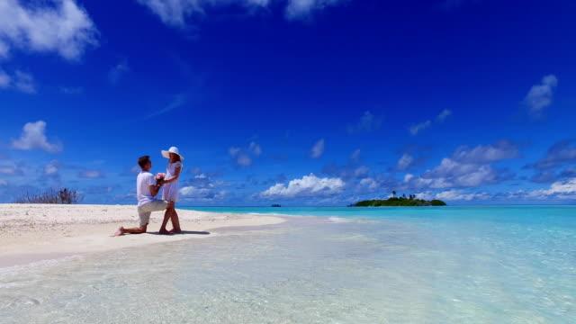 v07384-Malediven-weißen-Sandstrand-2-Menschen-junges-Paar-Mann-Frau-Vorschlag-Engagement-Hochzeit-Ehe-am-sonnigen-tropischen-Inselparadies-mit-Aqua-blau-Himmel-Meer-Wasser-Ozean-4k