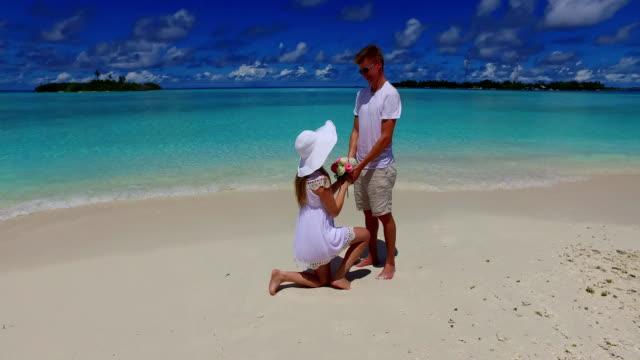 v07391-Maldivas-playa-2-personas-joven-pareja-hombre-matrimonio-mujer-propuesta-compromiso-boda-isla-paraíso-soleado-con-cielo-azul-aqua-agua-mar-4k