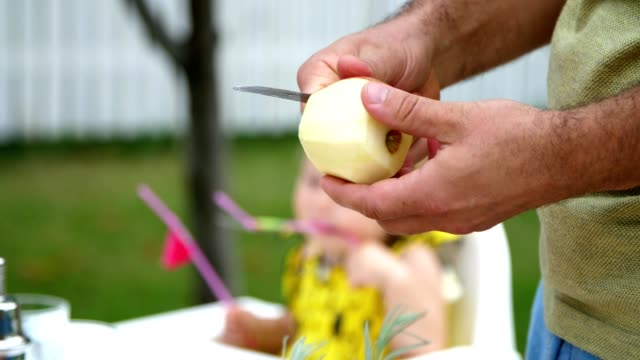 verano-en-el-jardín-lenta-primer-plano-las-manos-de-los-hombres-pelar-una-manzana-con-un-cuchillo-cortar-la-cáscara