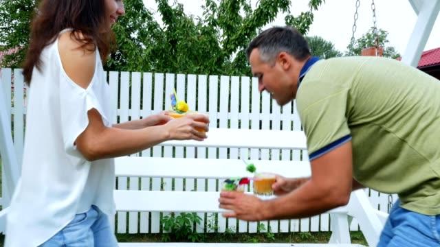 verano-en-el-jardín-los-padres-mamá-y-papá-lleva-recién-exprimido-zumo-de-fruta-a-tratar-a-sus-hijos-La-familia-pasa-su-tiempo-de-ocio-juntos