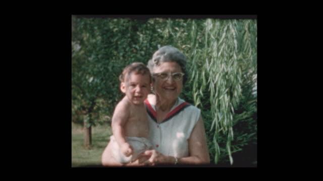 Portrait-of-elderly-grandmother-holding-baby-grandson
