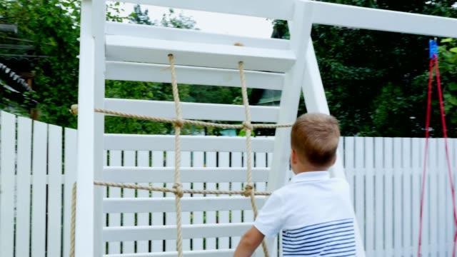 verano-en-el-jardín-niño-un-niño-de-cuatro-años-sube-escaleras-de-los-niños-en-el-patio-La-familia-pasa-su-tiempo-de-ocio-juntos