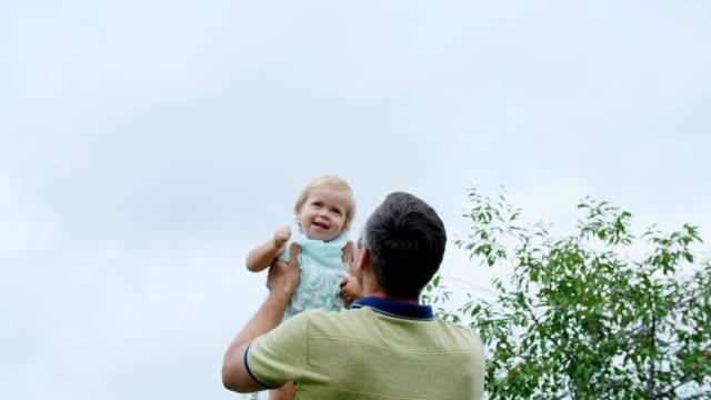 verano-en-el-jardín-madre-una-vista-desde-abajo-el-padre-lanza-a-su-hija-de-un-año-juega-con-ella-tiene-diversión-Ella-se-ríe-familia-pasa-su-tiempo-de-ocio-juntos