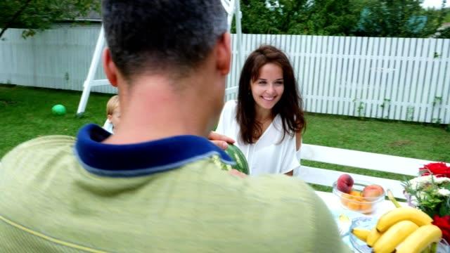 Una-familia-joven-con-dos-niños-divertidos-sentado-en-una-mesa-en-el-jardín-en-verano-Dad-corta-una-sandia-grande-va-a-tratar-a-su-familia-almuerzo-con-la-familia