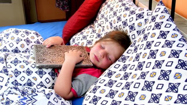 Niña-en-la-cama-Tryies-chica-Haz-dormidos-con-un-viejo-diario-de-padre-Niña-con-un-libro-viejo-en-la-cama-Concepto-de-familia