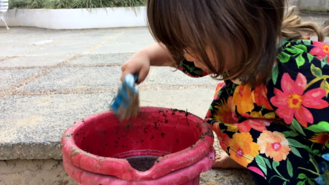 Candid-moment-of-little-girl-playing-with-toys-and-sandbox-tools-at-the-playground