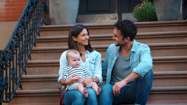 Young-couple-with-a-baby-sitting-on-front-stoop-close-up