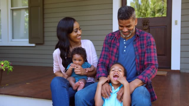 Family-With-Baby-and-Son-Sit-On-Steps-Of-Porch-In-Front-Of-Home
