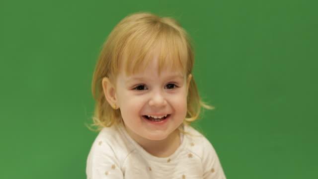 Sonrisas-de-niño-lindo-y-mostrando-su-lengua-Muchacha-hermosa-de-dos-años-Lindo-niño-rubio-Ojos-marrones-De-cerca-Fondo-de-pantalla-verde