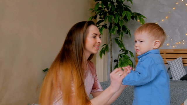 Glückliche-junge-Mutter-und-ihr-Baby-Sohn-spielen-togerher
