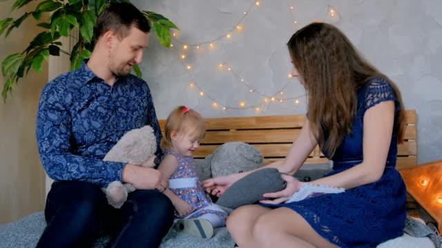 Felizes-jóvenes-padres-y-su-hija-jugando-togerher