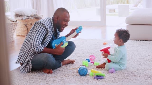 Junge-schwarze-Vater-Palying-Ukulele-mit-Sohn-im-Wohnzimmer