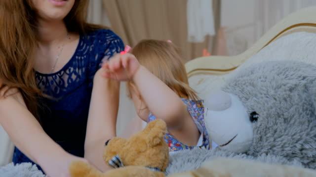 Joven-madre-y-su-hija-jugando-togerher-en-casa