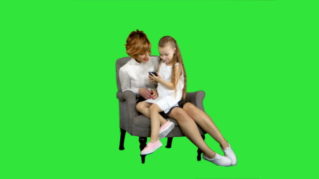 Mother-and-her-little-daughter-sitting-and-enjoy-the-phone-on-a-Green-Screen-Chroma-Key
