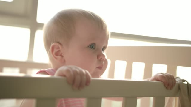 Cute-baby-standing-in-cot-Cute-childhood-Toddler-girl-in-crib