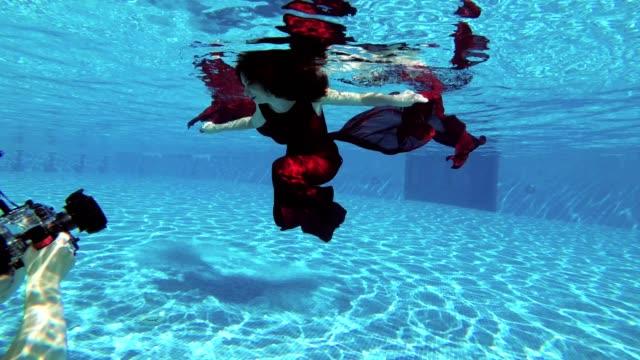 Un-fotógrafo-del-hombre-toma-una-cámara-submarina-profesional-novia-hermosa-chica-con-el-pelo-rojo-que-nada-bajo-el-agua-en-la-piscina-en-un-vestido-rojo-Cámara-lenta-