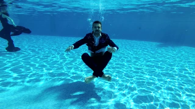 A-man-businessman-in-a-suit-and-a-white-shirt-dives-to-the-bottom-of-the-pool-under-the-water-He-sits-on-the-bottom-in-a-Lotus-position-looks-into-the-camera-and-lets-out-bubbles-Slow-motion-Action-camera-underwater-