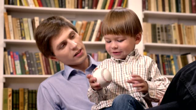 Little-boy-sitting-with-his-young-father-and-holding-ball-shelves-with-books-background