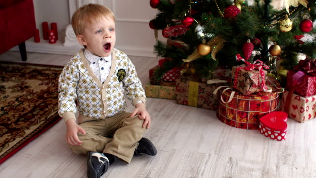 Child-is-sitting-near-the-Christmas-tree-and-yawns
