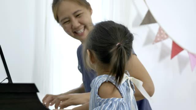4K:-lenta-de-chica-tocando-el-piano-con-su-madre