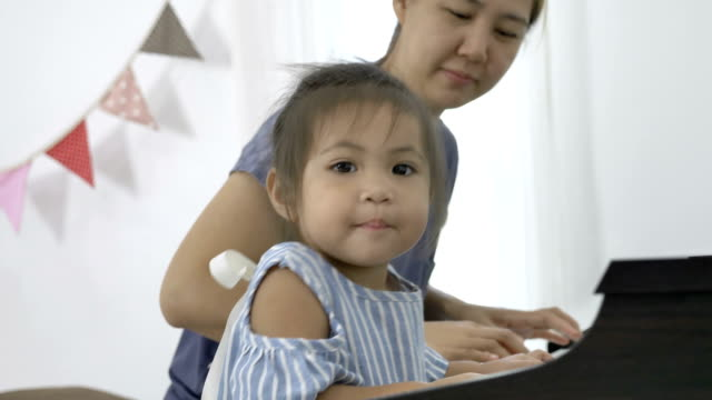 4K-:-Slow-motion-of-Asian-girl-playing-piano-with-her-mother