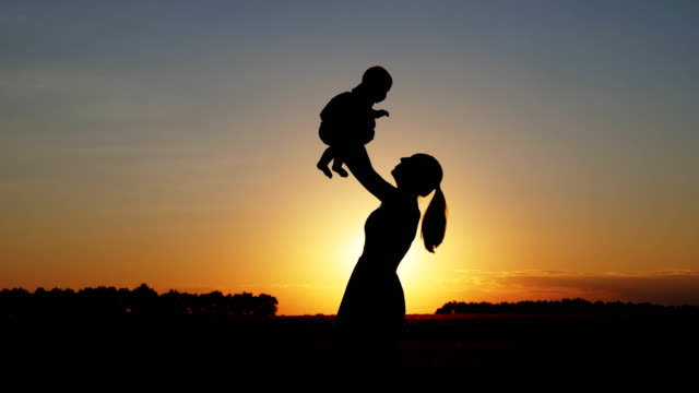 Silhouette-of-mother-with-child-at-sunset
