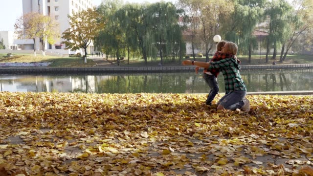Young-mother-having-fun-with-her-son-in-autumn-park-at-sunny-day