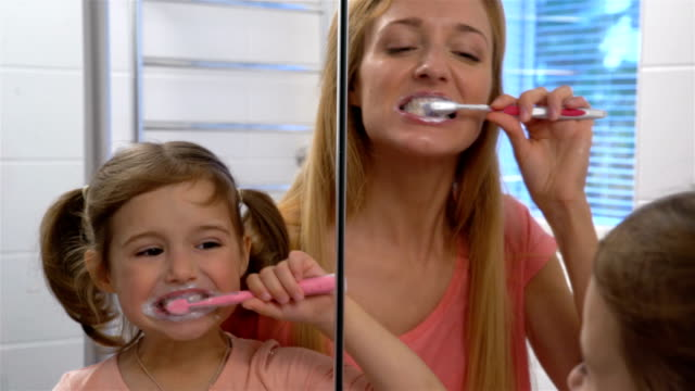 Young-attractive-mom-and-her-cute-daughter-brush-their-teeth-