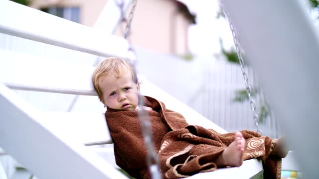a-little-one-year-old-girl-wrapped-in-a-towel-with-a-dirty-face-lonely-sitting-on-a-swing-in-the-garden-in-the-summer-She-has-a-sad-look-She-wants-to-sleep