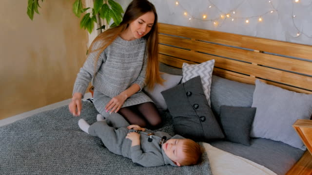 Happy-young-mother-and-her-baby-son-playing-togerher