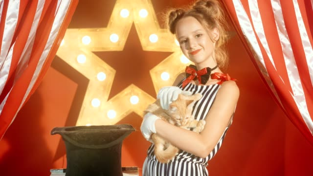 Cheerful-young-girl-magician-is-holding-kitten-in-hands