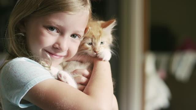 Una-niña-pequeña-y-sonriente-sosteniendo-un-mascota