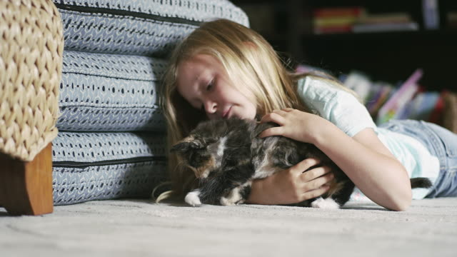 A-little-girl-laying-on-the-floor-and-petting-a-kitten-as-it-tries-to-get-away