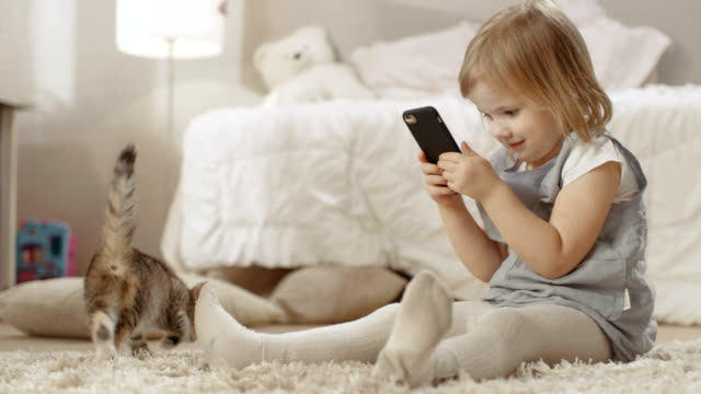 Cute-Little-Girl-Sits-on-the-Floor-with-Smartphone-and-Shoots-Video-of-Her-Striped-Kitten-Walking-Around-Slow-Motion-