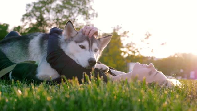 Schöne-junge-Frau-die-das-Spiel-mit-lustigen-husky-Hund-draußen-im-park